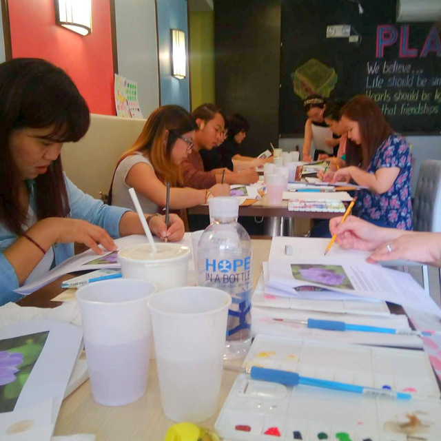 The students works on their individual flower paintings.